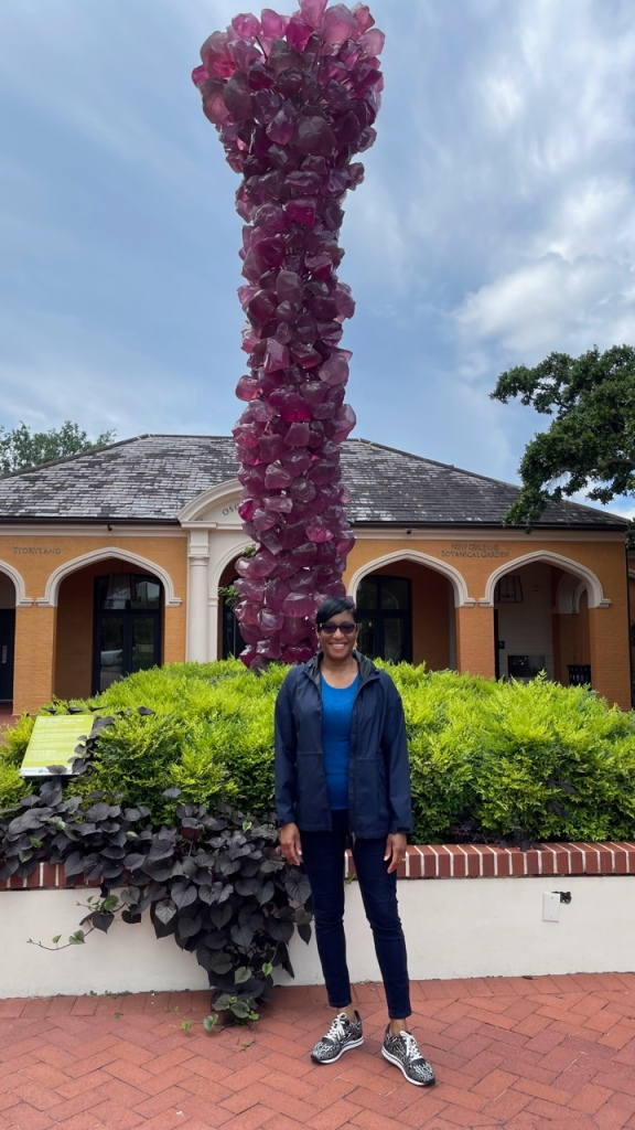 The author of this blog post, Leisure Lambie, stands in front of the Dale Chihuly Rose Crystal Tower at the entrance of the New Orleans Botanical Garden.